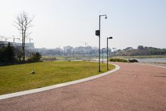 Curving lakeside red path with modern buildings in distance on s. Curving lakeside red-painted path with modern buildings in the distance on sunny winter day royalty free stock image