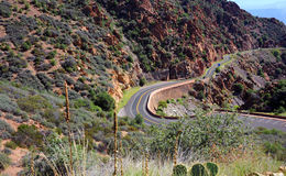 Curving Mountain Road. Winds its way to historic Jerome, Arizona, a western ghost town. Red rocky cliffs overhand highway stock images