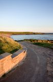 Curving path leading to a bay. A curving path leads down to a beautiful bay, with blue skies and a white lighthouse in the background Stock Photography