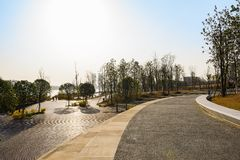 Curving path on slope at lakeside in sunny winter afternoon. Curving path on the slope at the lakeside in sunny winter afternoon,Tianfu New Area,Chengdu,China stock images