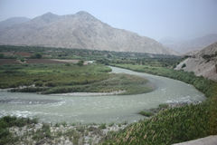 Curving Peruvian River. In the mountains with green brown and grey colored background Royalty Free Stock Image