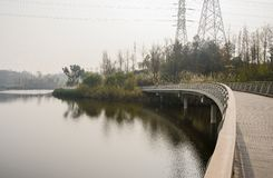 Curving planked footbridge over water in sunny winter afternoon. Curving planked footbridge over the water in sunny winter afternoon,Chengdu,China stock photography