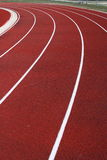 Curving race track. Curve of runner race track; shows red surface and white lines making the lanes Royalty Free Stock Images