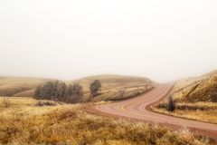 Curving red highway in a foggy Oklahoma. A highway curving between rolling hills dotted with green trees in a foggy countryside landscape in spring time USA stock images