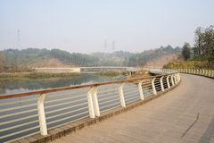 Curving riverside fenced and planked footbridge in sunny winter. Chengdu,China royalty free stock images