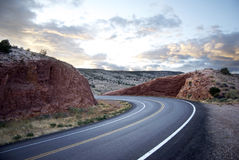 Curving road. At sunset between red rocks Royalty Free Stock Photography