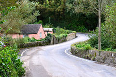 Curving Road. Along the side of a house in the rural area of the U.K. in the region of Devon.  Photo taken April 2014 Stock Images