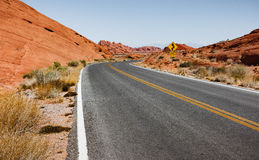 Curving Road Bordered by Red-brown Cliffs Royalty Free Stock Photography