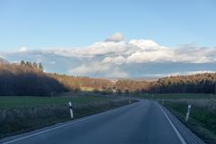Curving road between fields and trees in Germany Langgöns in Winter stock image