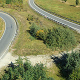 Curving roads in countryside. Aerial view of two curving or bending roads in green countryside royalty free stock photos