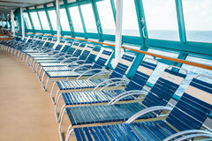 Curving Row of Blue and White Chaise Lounges. A row of blue and white chaise lounges in a curving row on the deck of a cruise ship royalty free stock photo