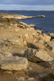 Curving shoreline with boulders and gravel along the Connecticut shoreline. Royalty Free Stock Images