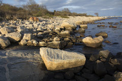 Curving shoreline with boulders and gravel along the Connecticut shoreline. Stock Photos