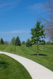 Curving Sidewalk. A photo of a curving footpath leading through a grassy knoll. There is a blue sky background Royalty Free Stock Photo