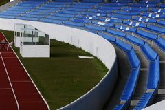 Curving stadium. Partial shot of running track with personel shelters on grass and blue seats in stadium Stock Images