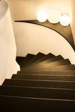 Curving staircase. Curving stone staircase with white walls and brown slate steps, three luminous orbs on a shelf, downward view Stock Photography