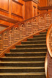 Curving Stairs with Green Carpet. A curving staircase in lobby with wood paneling and green carpet stock images