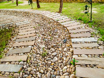 Curving stone path in grassy field Stock Photo