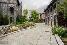 Curving stone-paved path in old-fashioned buildings on cloudy da. Curving flagstone paved path in old-fashioned buildings on cloudy spring day,Qingyan town royalty free stock photos