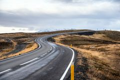 Winding Road in a Mountain Scenery and Cloudy Sky. Curving Uphill Road in Iceland under Overcast Sky in Autumn royalty free stock photography