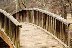 Curving Wood Bridge Over Stream Royalty Free Stock Photography