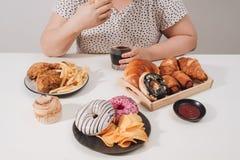 Curvy żeński narządzanie jeść hamburger, przejada się problem, depresja obrazy stock