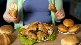 Curvy żeński narządzanie jeść kurczaka i chleba przejada się problem, depresja obrazy royalty free