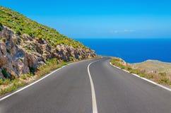 Curvy дорога асфальта водя к изумительному заливу моря стоковые фото