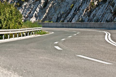 Curvy asphalt road. With stone rocks in background Royalty Free Stock Images
