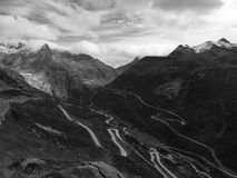 Curvy black and white mountain road. Curvy mountain road in the alps. Black and white picture Royalty Free Stock Photography