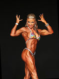 Curvy Blonde Bodybuilder. Curvy blonde bombshell Hannah Braden shows off her buff bodybuilder body as she competes in the Women's Physique competition finals at Royalty Free Stock Image