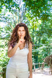Curvy classy mature woman asks for silence. Curvy classy mature woman puts index finger to lips asking for silence in a garden Stock Photos