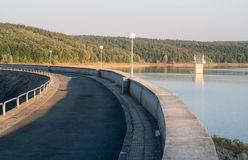 Curvy concrete dam wall. With water and forest on background Royalty Free Stock Image