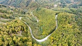 Curvy droga w zielonym lesie, niscy wzgórza Sistani jesień błękit długa natura ocienia niebo Zdjęcie Stock