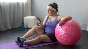 Curvy Frau, die Ergebnisse des on-line-Abnehmenmarathons nach Haupttraining überprüft lizenzfreie stockbilder