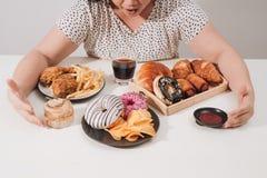 Curvy Frau, die sich vorbereitet, Hamburger, Zu viel essen Problem, Krise zu essen stockfotos