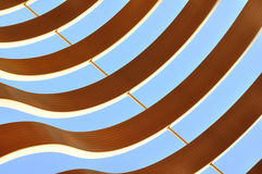 Curvy graphic abstract pattern. Curvy architectural wooden graphic abstract pattern against blue sky stock image