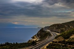 Curvy highway at the edge of a cliff with ocean below. Curvy road at the edge of a cliff with ocean below on a cloudy autumn day Stock Photo