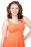 Curvy junge Frau, die orange Kleid, glückliches Lächeln trägt lizenzfreies stockfoto