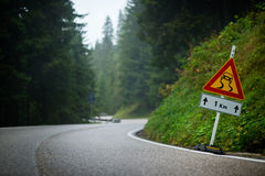 Curvy mountain road with slippery route sign Royalty Free Stock Photography