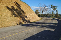 Curvy mountain road with tree shadow Stock Photos