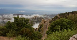 Curvy Mountain Road Winding Around Boulders and forest amongst Clouds. In Arizona Stock Images