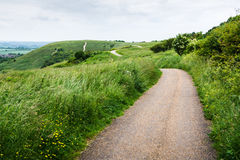 Curvy path on hilly landscape on cloudy day Royalty Free Stock Photography