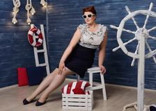 Curvy pin-up girl. On the boat at summer royalty free stock photography