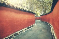 Curvy red walls passage surrounded by bamboo forest. Curvy red wall passage surrounded by bamboo forest, color toning applied, Wuhou Temple, Chengdu, China Royalty Free Stock Images