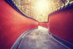 Curvy red walls passage surrounded by bamboo forest. Curvy red walls passage surrounded by bamboo forest, color toning applied, Wuhou Temple in Chengdu, China Stock Photo