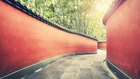 Curvy red walls passage surrounded by bamboo forest. Curvy red walls passage surrounded by bamboo forest, color toning applied, Wuhou Temple in Chengdu, China Royalty Free Stock Photography