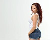 Curvy redheaded kvinna i ärmlös tröja och kortslutningar Arkivbild