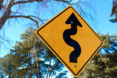 Curvy road ahead sign with trees in the background.  royalty free stock photography