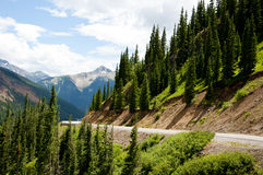 A curvy road amid snow capped mountains. Royalty Free Stock Photos